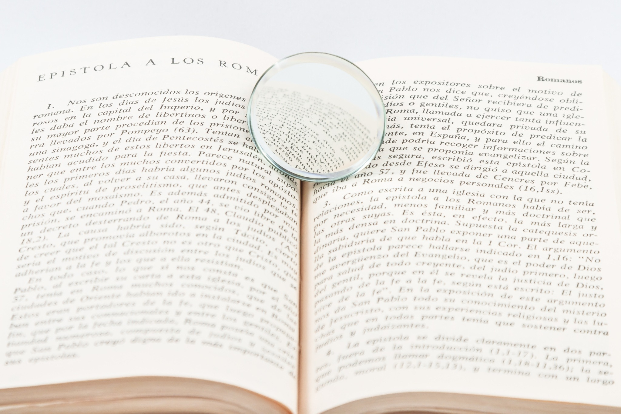 105478589-magnifying-glass-over-top-open-book-on-white-backg