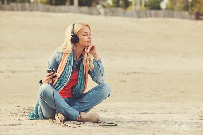 Beautiful blonde with headphones listening to music