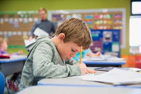 95131919-focused-elementary-student-writing-at-desk-in-classroom