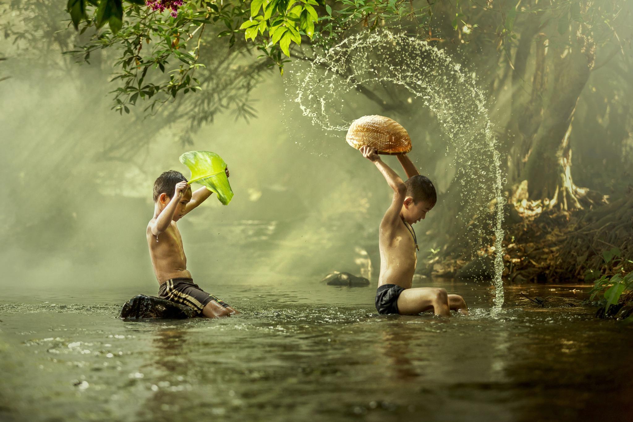 Thai boys splashing whit in a river.