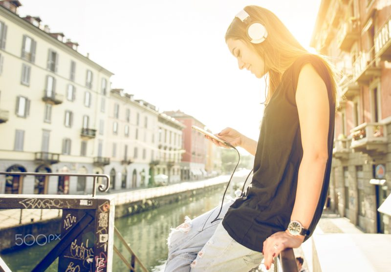 woman listening to music with headset and smartphone in Milan. concept about technology and youth
