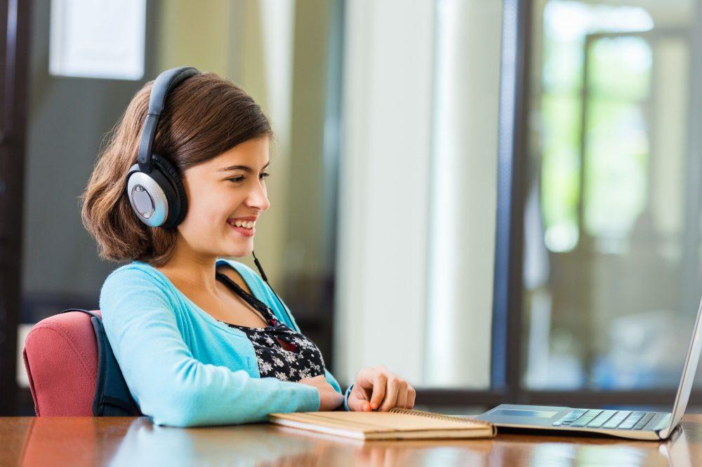 preteen-girl-doing-homework-while-listening-to-headphones-529980621-58dcf1653df78c516288ec77